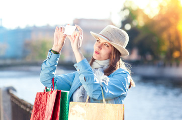 Beautiful girl with shopping bags taken picture of herself in th