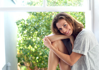 Attractive woman smiling by window at home