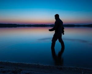 Man standing in lake water at sunset