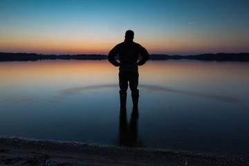 Man standing in lake water at sunset