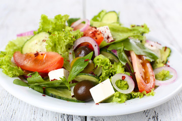 Greek salad in plate on color wooden table background