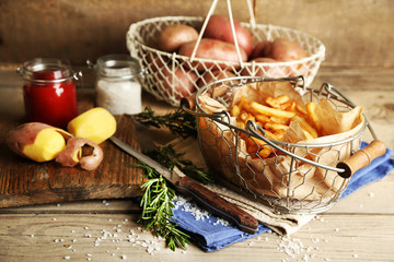 Tasty french fries and fresh potatoes in metal baskets
