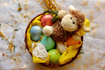 Easter lamb with colored pearly eggs in basket