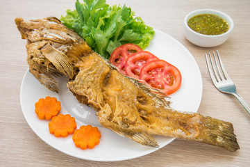 Fried fish with vegetables on plate and sauce