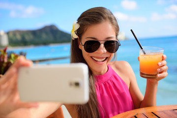 Selfie woman drinking drink at beach vacation bar