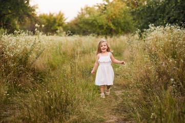 Маленькая девочка улыбается и идет в поле