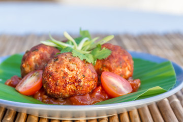 meat balls with tomato served on palm tree leaf