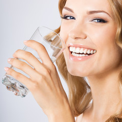 Young happy woman drinking water, over grey