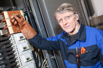 Senior electrical service repairman turning off main switcher
