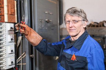 Electrcian maintainer holds pliers in hand wearing rubber glove