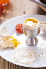Soft-boiled egg in the morning with pepper, tomatoes and crouton