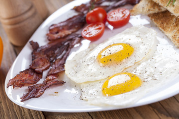 Delicious fried egg with spices, bacon, croutons and tomatoes on