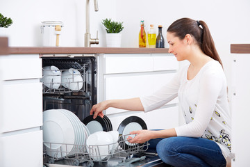 20s woman in kitchen, empty out the dishwasher