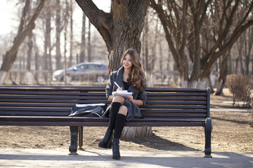 Schoolgirl sitting on a bench with a notebook in the spring park