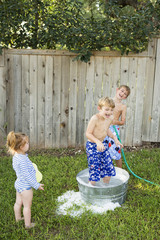 Three children playing in a garden with a water-filled tub and hose.