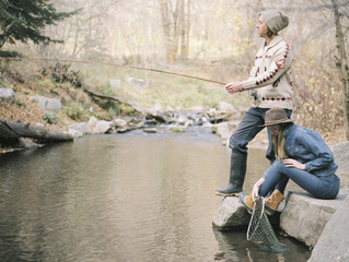 Young couple in a forest, fishing in a river.