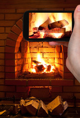 tourist photographs of burning wood in fireplace