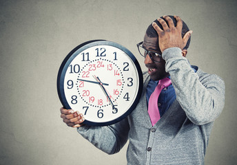 Stressed young man running out of time looking at wall clock