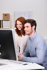 kollegen schauen zusammen auf computer
