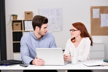 zwei kollegen im büro schauen sich an