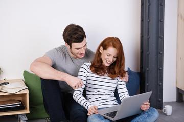 modernes paar sitzt mit notebook auf dem fußboden