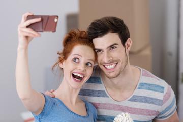 lachendes paar macht ein selfie beim umzug