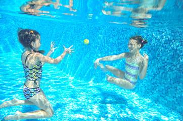 Happy children swim in pool underwater, girls swimming
