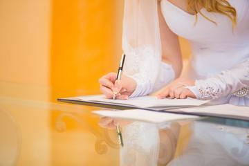 bride putting signature into wedding certificate