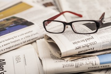 News. reading glasses lie on newspaper pile