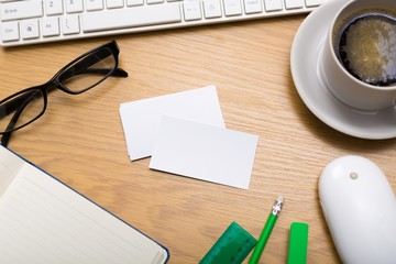 Desk. Blank business cards with supplies and coffee cup on
