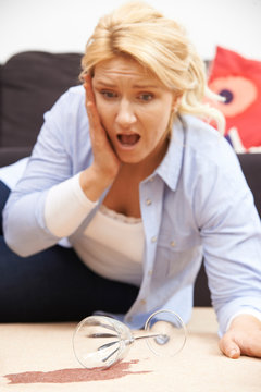 Woman Accidentally Spilling Red Wine On Carpet At Home