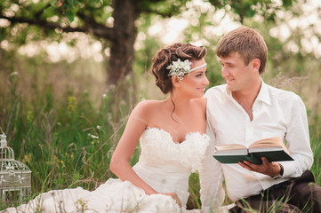 The bride and groom in nature and relax reading a book