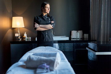 Massage therapist standing by massage table with hands crossed