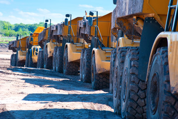 Row of dump trucks driving through construction zone