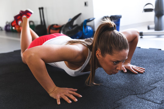 Female with nice body  doing  some push ups a the gym
