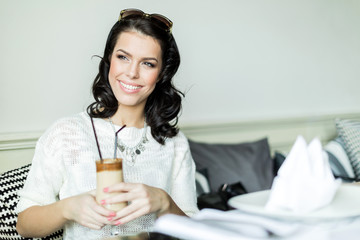 Gorgeous  lady smiling in a restaurant while holding her coffee