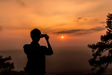 Shilouette of man taking a photo of sunset with smartphone.