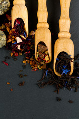 assortment of tea in scoops on black stone background
