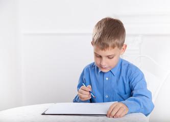 beautiful, caucasian boy draws a pencil on the album