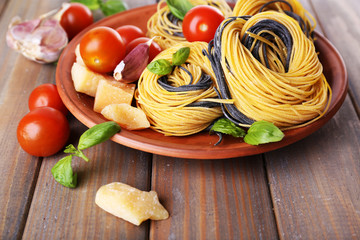 Raw pasta with cheese and vegetables on plate on table close up