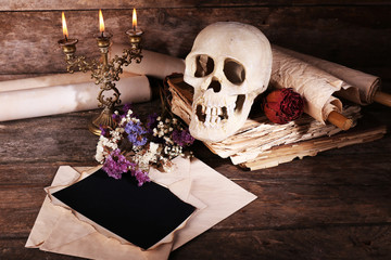 Still life with human skull, retro book and candlelight