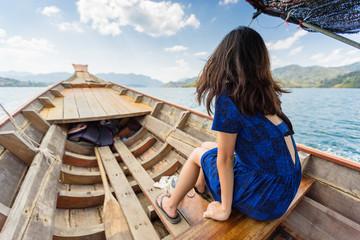 Girl sitting in longtail boat sailing through huge lake