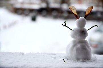 little snowman standing on the veranda of the house