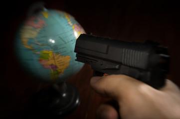 Terrorist put a gun to globe.