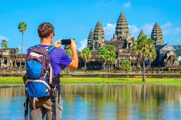 Young man is taking a photo of Angkor Wat temple, Cambodia