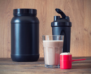 Whey protein powder in scoop  and plastic shaker