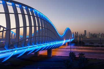 Meydan Bridge illuminated at night. Dubai, UAE