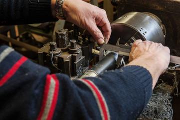Braccia di  un artigiano che usano il tornio