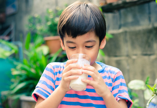 Littl boy drinking milk in the park vintage color style