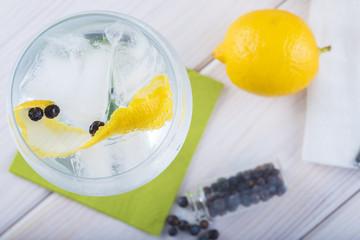 Gin tonic en copa de balón con twist de limón y bayas de enebro